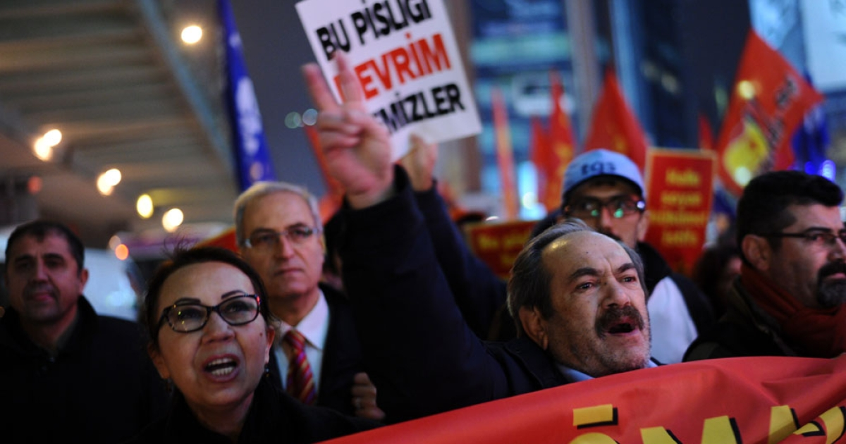 A Turkish protester holds up a placard reading