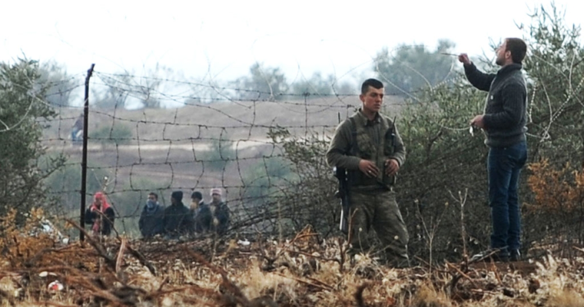 Syrian refugees cross the border into Turkey as a Turkish soldier watches on Jan. 15, 2014, near the Oncupinar border crossing and Kilis.</p>