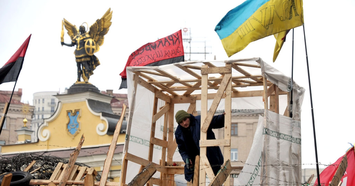 A pro-EU protester fixes a barricade on Independence square in Kyiv on January 16, 2014.</p>