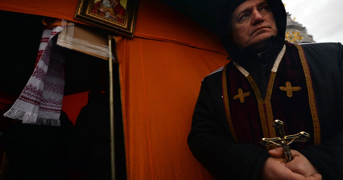 A Ukrainian Greek Catholic Church priest holds a crucifix outside a tent church in Kiev's Independence Square on December 7, 2013.</p>