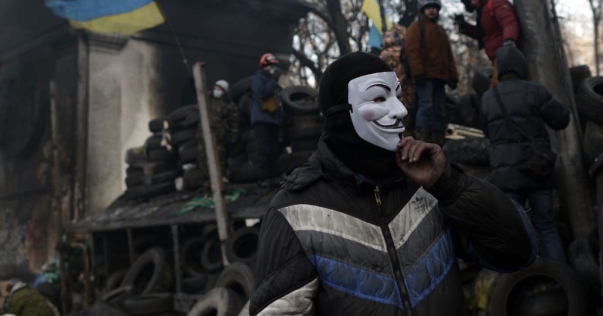 An anti-government protester, wearing a Guy Fawkes mask, rests at a road block in Kyiv on Jan. 26, 2014.</p>
