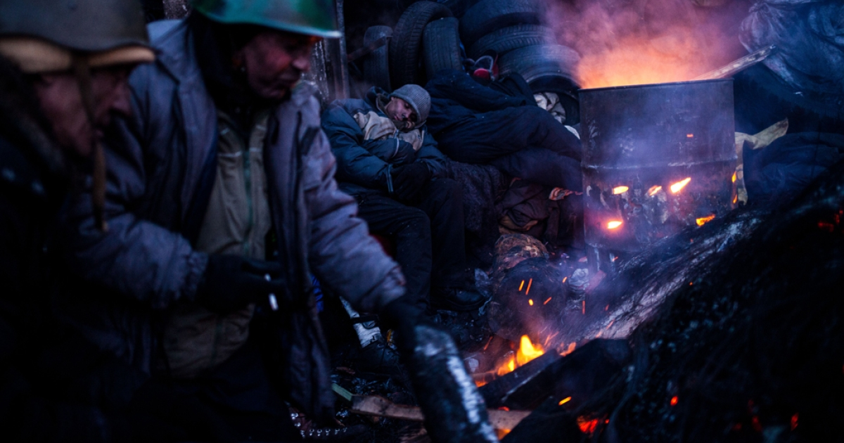 Anti-government protesters warm themselves at a fire near a barricade early morning in Kyiv on January 31, 2014.</p>