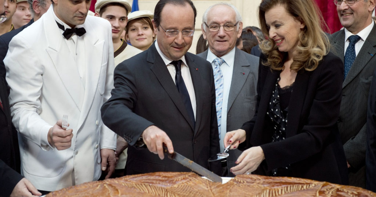 French President Francois Hollande and his companion Valerie Trierweiler slice a traditional epiphany cake on January 7, 2014 at the Elysee palace, in Paris.</p>