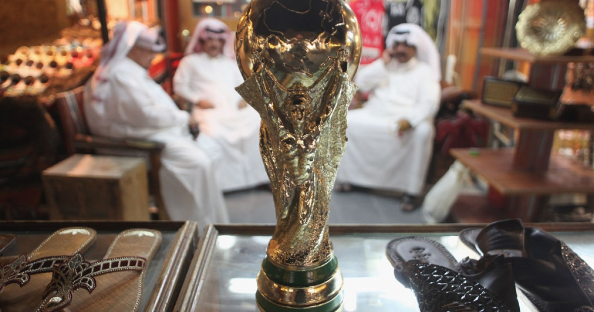 Arab men sit at a shoemaker's stall with a replica of the FIFA World Cup trophy on October 24, 2011 in Doha, Qatar. Qatar will host the 2022 FIFA World Cup.</p>