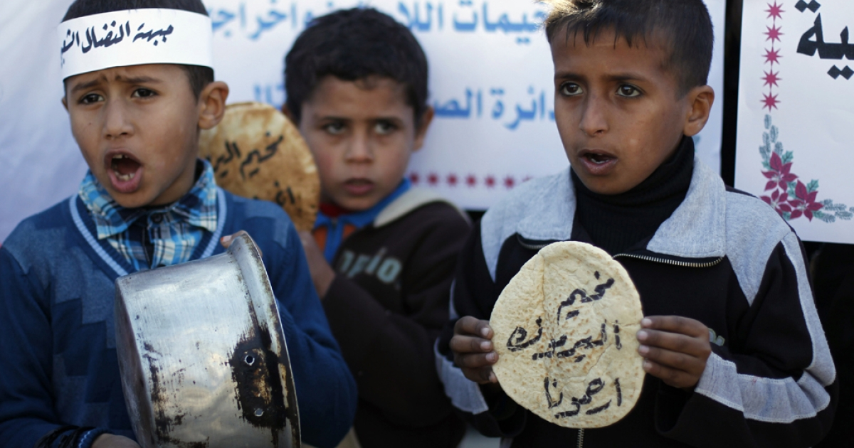 Palestinians children holds bread and pots on January 8, 2014, as they take part in a protest against the poor living conditions at the Yarmuk refugee camp in the Syrian capital Damascus in Gaza Strip.</p>