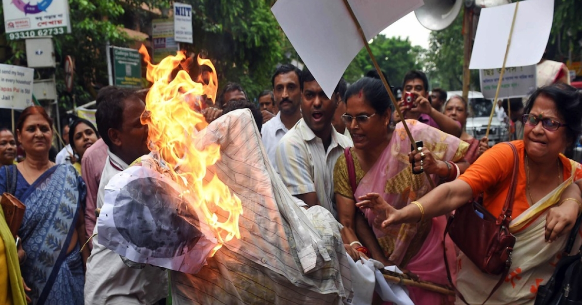In this photograph taken on July 1, 2014 Indian protestors burn an effigy of Trinamool Congress MP Tapas Pal in Kolkata. Protestors set fire to an effigy of an Indian lawmaker who had threatened the rape of his rivals' relatives as a storm over his comments refused to subside despite an apology.</p>