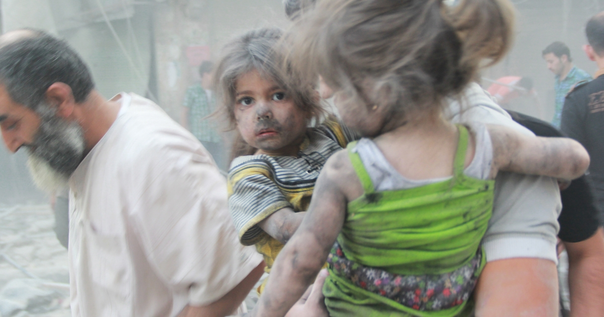 A Syrian man carries two girls covered with dust following a reported air strike by government forces in Aleppo.</p>