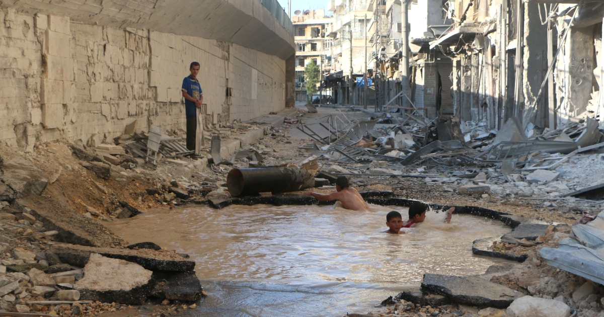 Syrian children play in a bomb crater flooded with water from a broken mains in the northern city of Aleppo.</p>