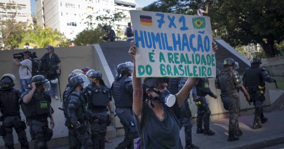 Police stand guard on the sidelines of an anti-World Cup protest near Maracana stadium on the last day of the World Cup soccer tournament,  July 13, 2014 in Rio de Janeiro, Brazil.  Anti-World Cup protesters criticize that the government should spend money on improvements for education, health and housing, instead of soccer.</p>