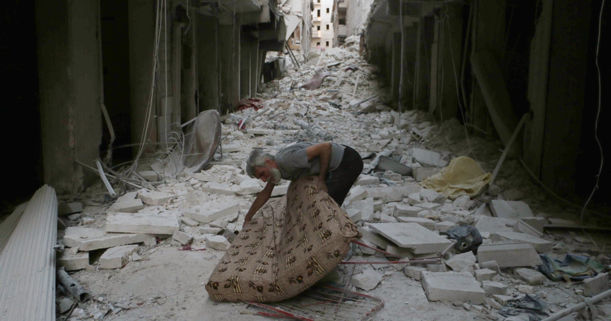 A Syrian resident grasps a mattress amid rubble following a reported overnight air strike by government forces on July 14, 2014 in the al-Firdous neighborhood of the northern city of Aleppo.</p>
