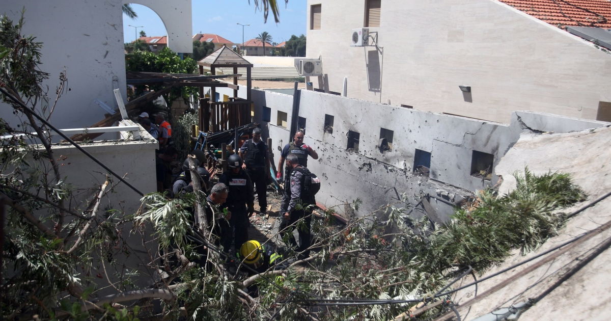 Emergency workers and Israeli security check a house damaged by a rocket fired by militants from the Gaza Strip, on July 16, 2014, in the city of Ashkelon.</p>