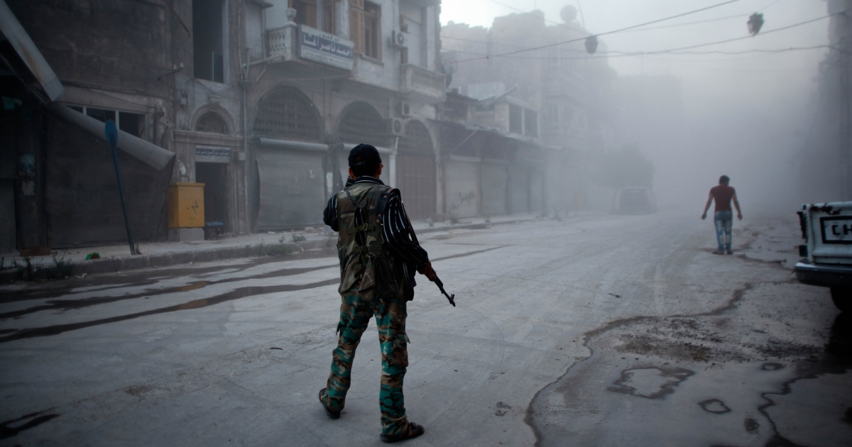A rebel fighter stands on a street covered with dust following a reported air strike by Syrian government forces in the old city of Aleppo.</p>