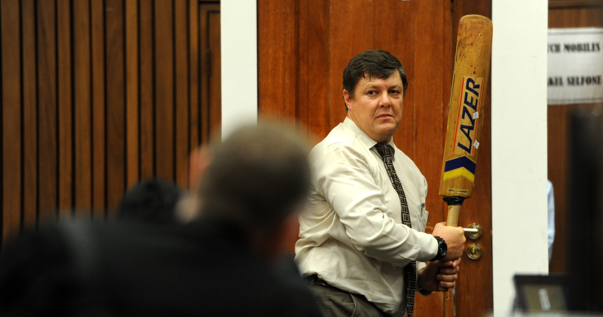 Police forensic expert Colonel Johannes Vermeulen holds a cricket bat while standing next to a replica door in the Oscar Pistorius trial.</p>