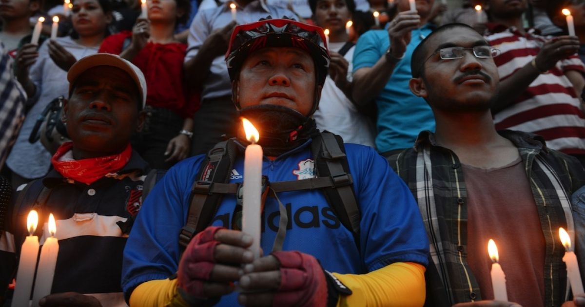Nepalese people hold candles in memory of the 16 Nepalese Sherpa guides killed in an avalanche on Mount Everest in Katmandu on April 30, 2014. An unprecedented shutdown of Mount Everest after the worst ever accident on the world's highest peak has left grieving Nepalese Sherpa guides and their families fearing for their livelihoods. The avalanche on April 18 that tore through a group of Sherpas — who were hauling gear up the mountain for their foreign clients before dawn — left 16 people dead and three others seriously wounded.</p>