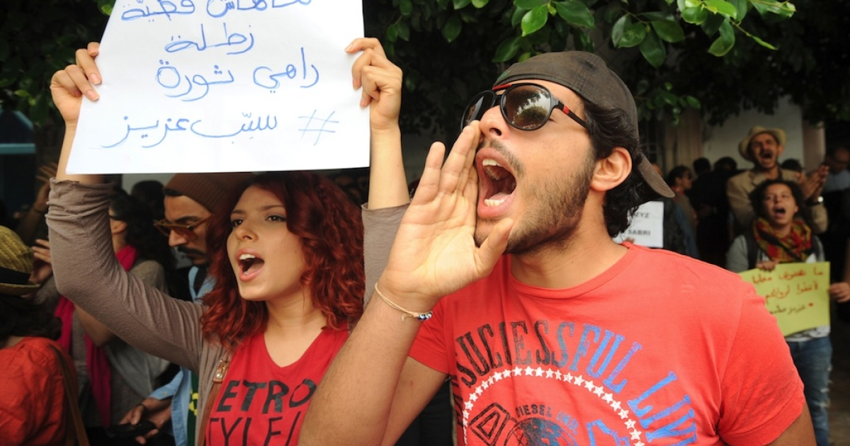 Tunisians shout slogans as they protest in front of the courthouse where renowned blogger Azyz Amani, who was active during the 2011 revolution, appeared on May 23, 2014, in Tunis. Amani was in court on charges of consuming cannabis as a campaign demanding changes to a law, seen as repressive, grows.</p>