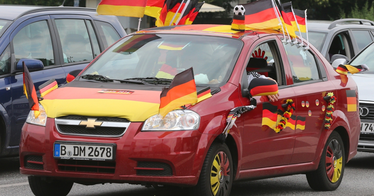 German flags are placed on a car on July 9, 2014 in Berlin.</p>