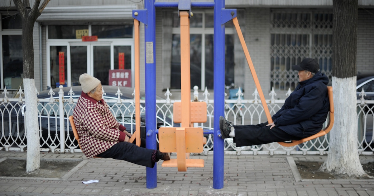 An elderly man and woman work out with gym equipment by a street in Beijing. Because of demographics and development, many of China's retirees are struggling to get by.</p>