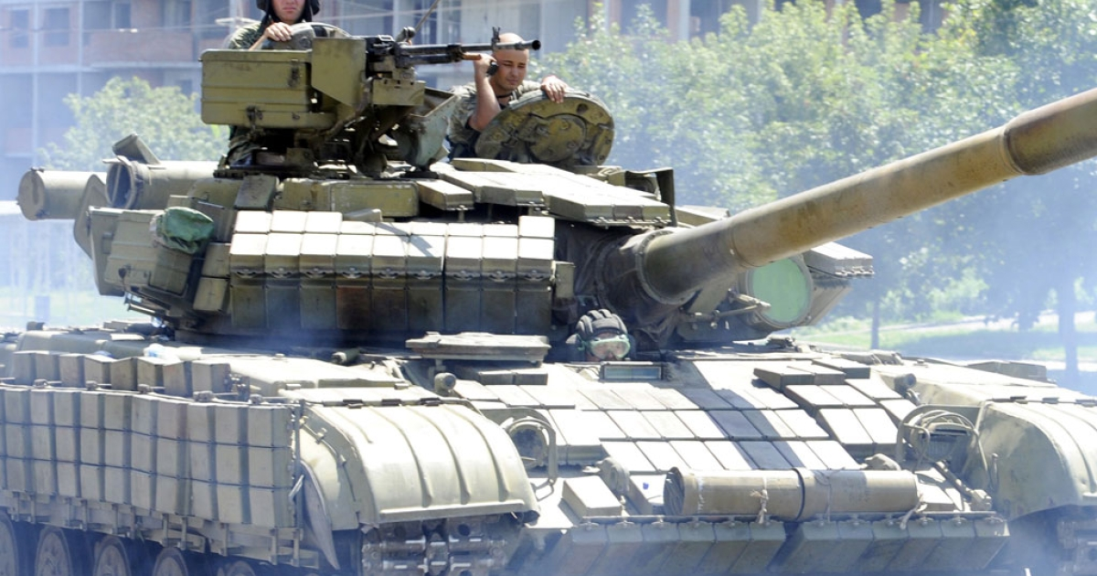 Pro-Russian militants drive a tank in the eastern Ukrainian city of Donetsk on July 21, 2014.</p>