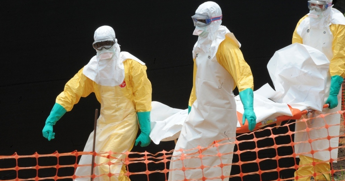 Workers with Doctors without Borders carry the body of a person killed by the Ebola virus.</p>