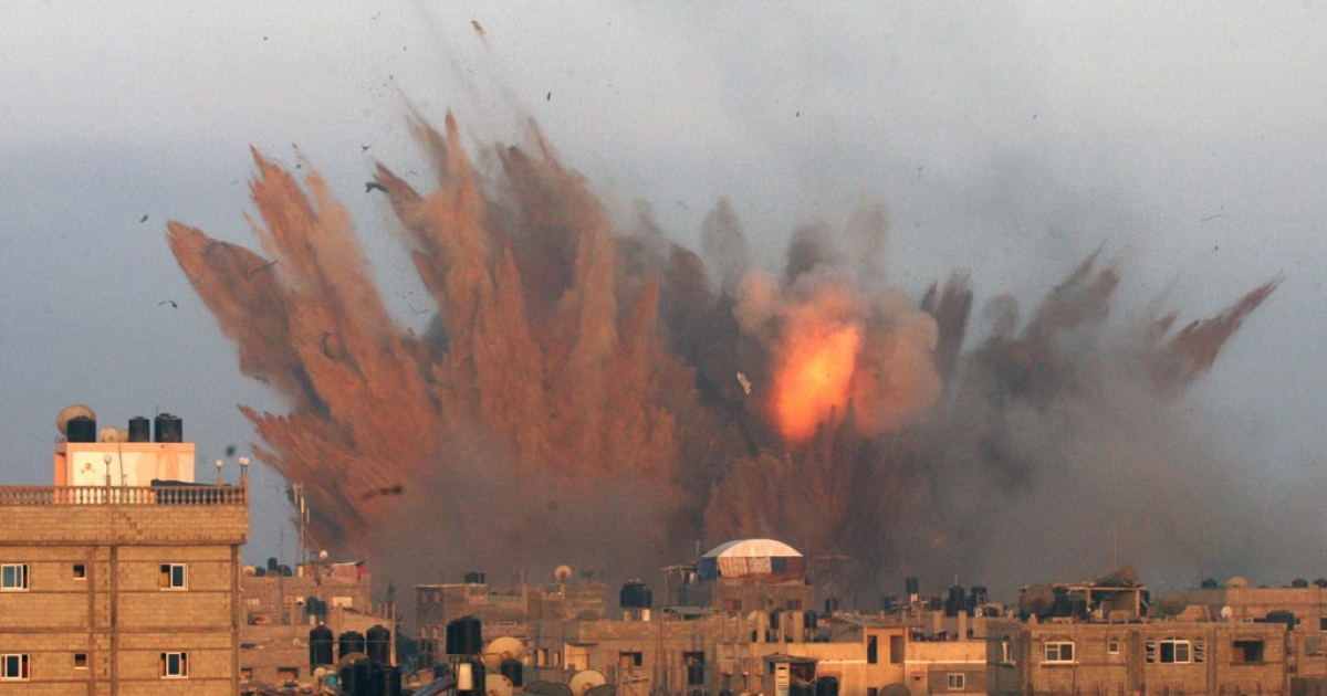 A ball of fire is seen following an Israeli air strike, on July 11, 2014 in Rafah, in the southern Gaza Strip.</p>
