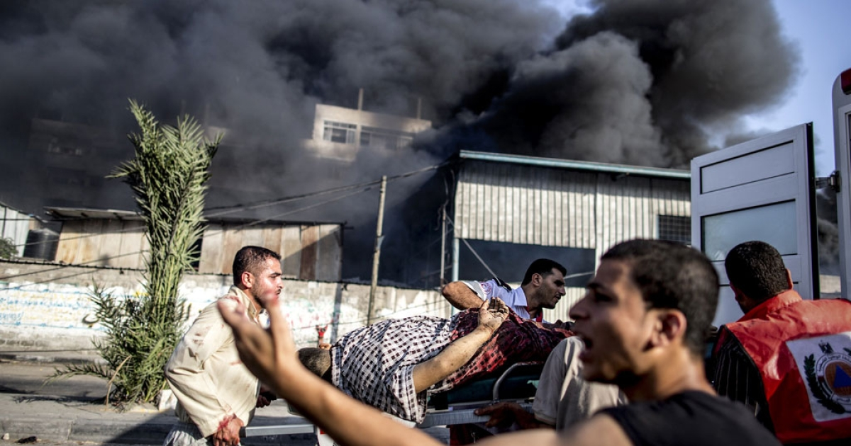 Palestinian emergency personnel evacuate a wounded man following an Israeli military strike on a market place in the Shejaiya neighborhood near Gaza City, on July 30, 2014.</p>