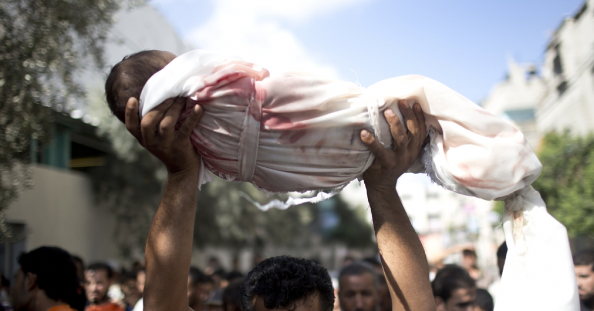A Palestinian man carries the body of a one-year-old baby Noha Mesleh, who died of wounds sustained after a UN school in Beit Hanun was hit by an Israeli tank shell, during her funeral in Beit Lahia, northern Gaza Strip, on July 25, 2014. Fifteen people were killed when Israeli fire hit a UN-run school in Gaza, raising the Palestinian toll on the 17th day of the conflict to 777, medics said.  AFP PHOTO/ MAHMUD HAMS        (Photo credit should read MAHMUD HAMS/AFP/Getty Images)</p>