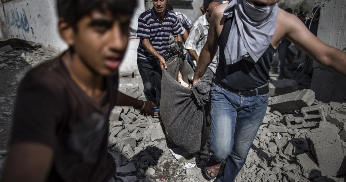 Palestinian recover the body of a man killed when his home was hit the previous night by Israeli fire in the northern district of Beit Hanun in the Gaza Strip during an humanitarian truce, on July 26, 2014.</p>