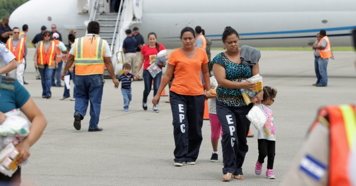 Women and their children walk on the tarmac after being deported from the US at the airport in San Pedro Sula, Honduras.</p>