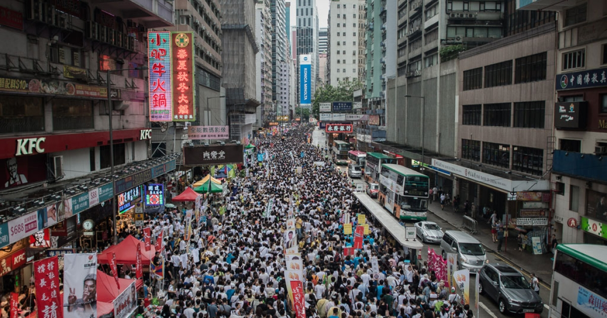 Protesters march during a pro-democracy rally in Hong Kong on July 1, 2014 as frustration grows over the influence of Beijing on the city.</p>