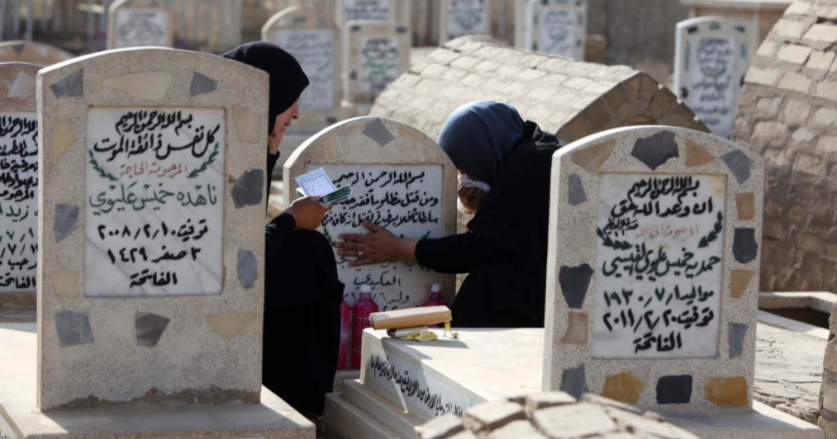 Mourners visit a Baghdad cemetery in 2013.</p>