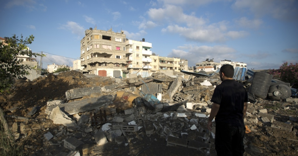 A Palestinian man inspects damage after overnight Israeli air strikes on July 3, 2014 in Gaza City.</p>