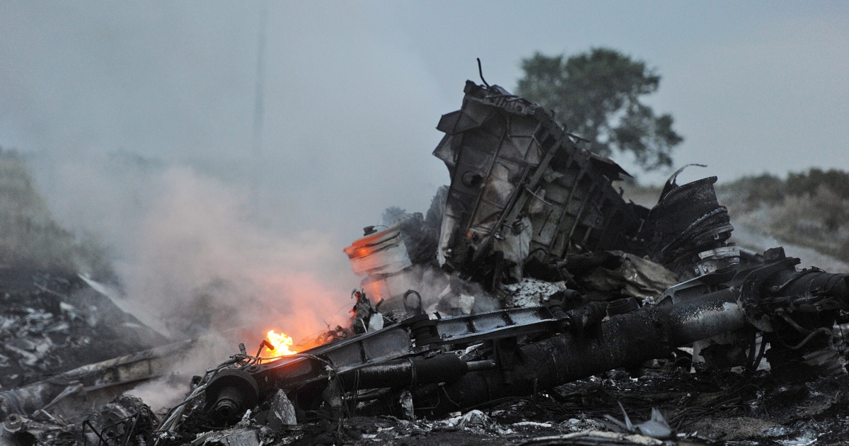 A picture taken on July 17, 2014 shows flames amongst the wreckages of the malaysian airliner carrying 295 people from Amsterdam to Kuala Lumpur after it crashed, near the town of Shaktarsk, in rebel-held east Ukraine. Pro-Russian rebels fighting central Kiev authorities claimed on Thursday that the Malaysian airline that crashed in Ukraine had been shot down by a Ukrainian jet. The head of Ukraine's air traffic control agency said Thursday that the crew of the Malaysia Airlines jet that crashed in the separatist east had reported no problems during flight. AFP PHOTO/DOMINIQUE FAGET        (Photo credit should read DOMINIQUE FAGET/AFP/Getty Images)</p>