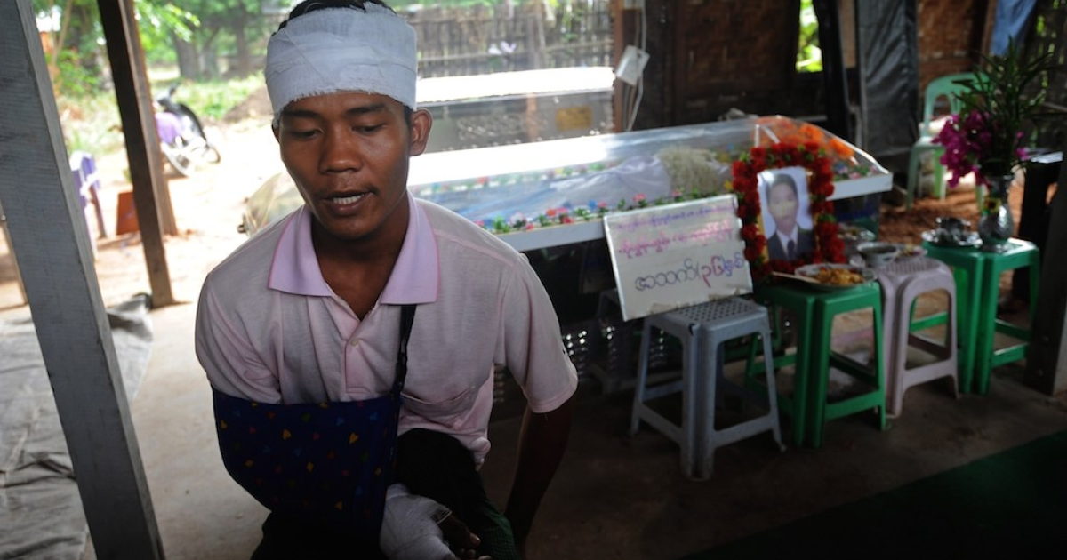 Ko Htwe, 24 , who was injured in recent sectarian clashes, talks during an interview next to a coffin holding his friend Tun Tun, 36, killed during a recent riot, before his funeral service in Mandalay, central Myanmar on July 4, 2014. Myanmar police imposed an overnight curfew in the country's second largest city of Mandalay on July 3, after two nights of sectarian unrest that left two people dead.</p>