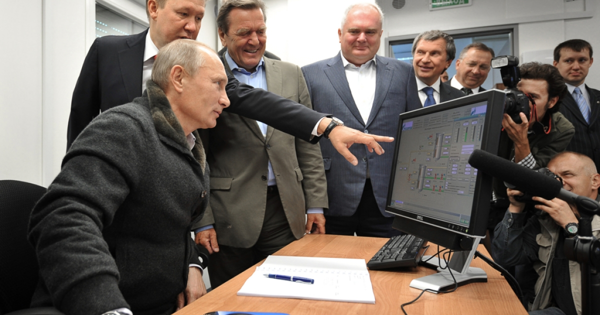 Russian Prime Minister Vladimir Putin (L),Gazprom Chief Executive Officer Alexei Miller (2nd L) and former German chancellor Gerhard Schroeder (3rd L) look at a screen as they attend the inauguration of the Nord Stream Project information mount at the gas compressor station