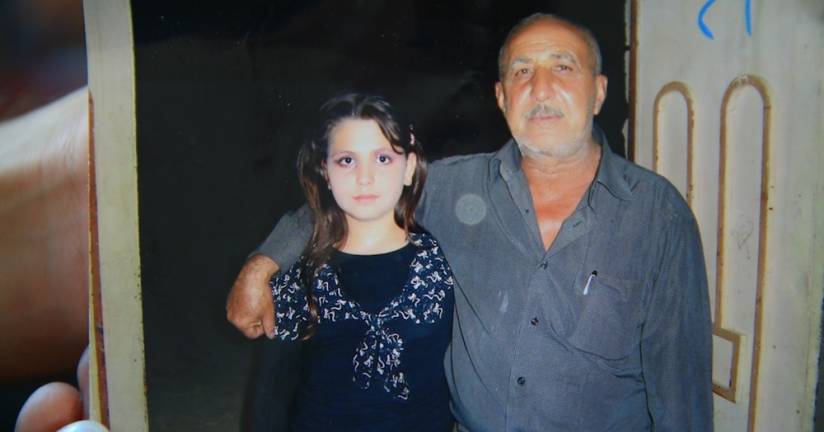 Dunya, aged 12 at the time, stands with her father.</p>