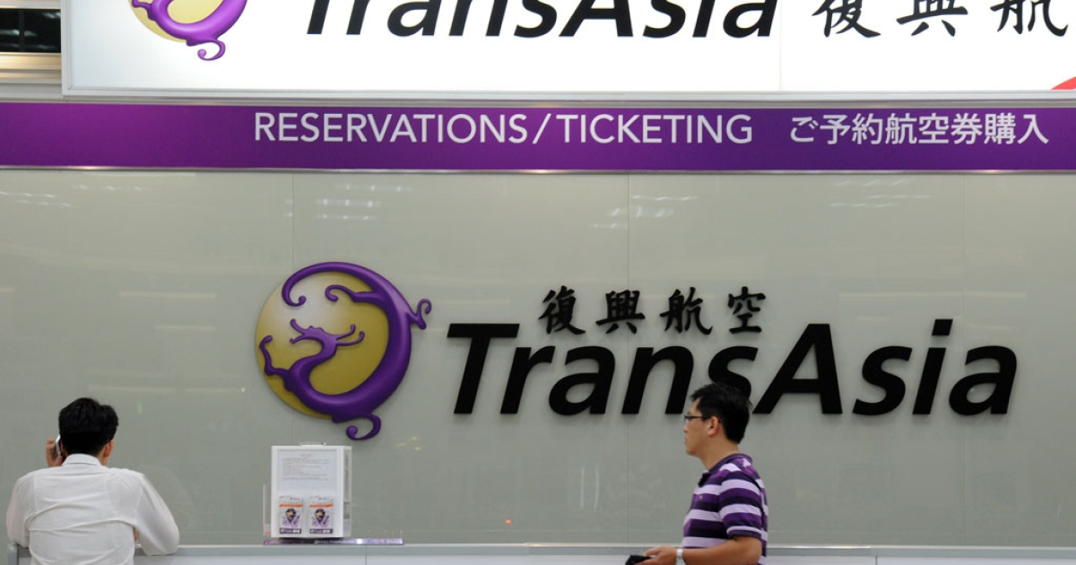 Local journalists wait in front of a TransAsia reservations desk at the Sungshan airport in Taipei on July 23, 2014.</p>