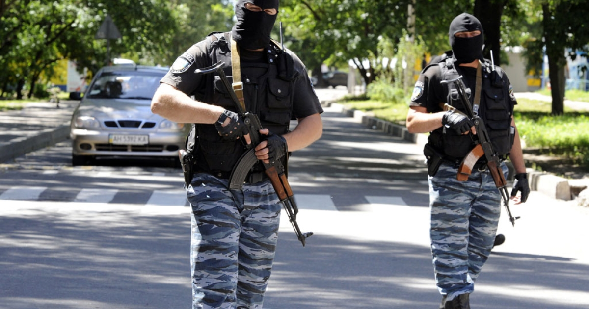 Masked armed men wearing uniforms with the emblem of the Berkut, Ukraine's disbanded elite riot police force, block the road near the police station in the center of the eastern Ukrainian city of Donetsk on July 1, 2014.</p>