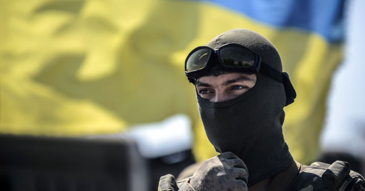 A Ukrainian soldier gestures as he stands guard with the Ukrainian flag behind him at a checkpoint in the Donetsk region in eastern Ukraine, on July 31, 2014.</p>