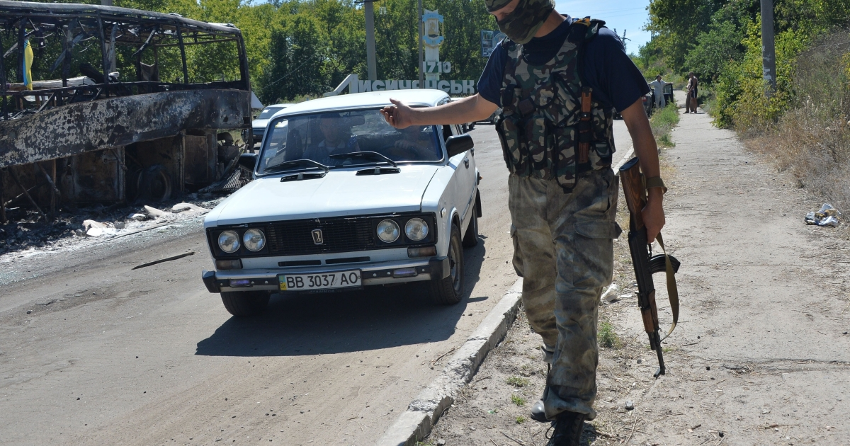 A pro-government volunteer checks passing cars near the eastern Ukrainian city of Lisichansk. Insurgents said Ukraine's military on Monday seized control of part of the site where Malaysian airliner MH17 crashed.</p>
