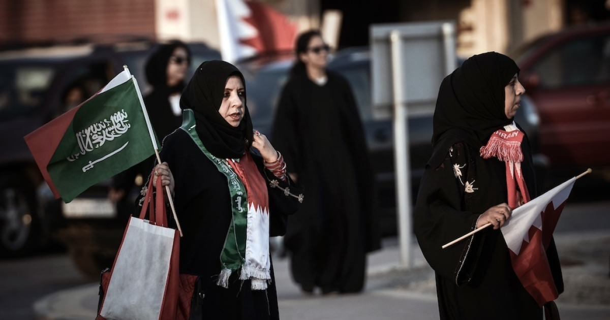 Bahraini women hold Bahrain and Saudi flags during a pro-government rally in the village of Arad on the Bahraini island of Muharraq on February 21, 2013.</p>
