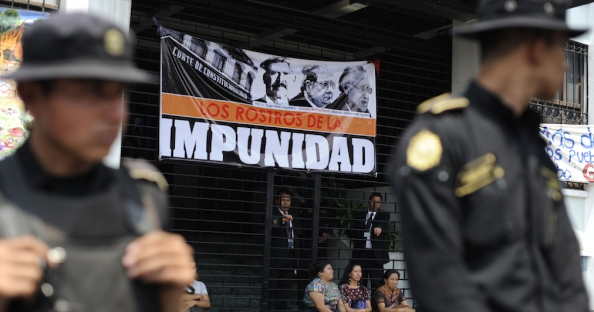 Police officers guard the entrance of the Constitutional Court (CC) of Guatemala, during a protest against the quashing of the 80-year sentence for genocide of former Guatemalan dictator General Efrain Rios Montt on May 24, 2013 in Guatemala city. Rios Montt will go back on trial after the nation's highest court threw out his genocide and war crimes conviction in the latest twist in complex proceedings.</p>
