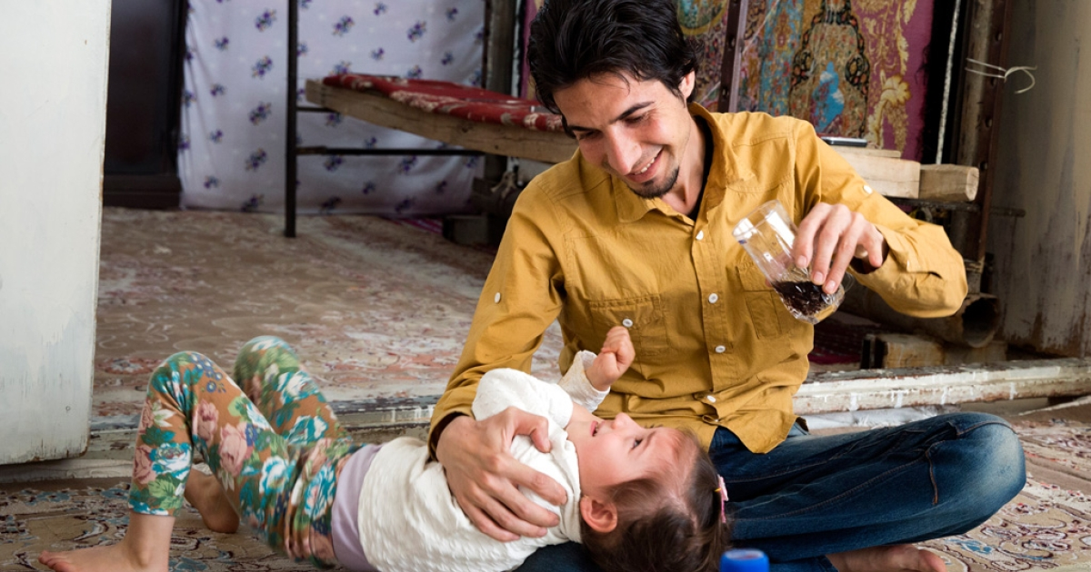 Mohsen Bakhshan, 24, plays with his daughter Mobina at their house in Qom, south of Tehran. He used to work in Qom but he has been unemployed for more than two years.</p>