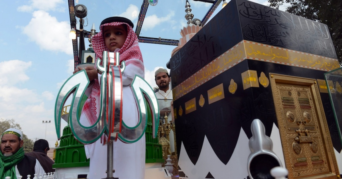 A Pakistani child stands next to a replica of the Kaaba, the Grand Mosque in the holy city of Mecca, during celebrations marking Eid Milad-un-Nabi, the birthday of Prophet Mohammed, in Lahore on January 14, 2014.</p>