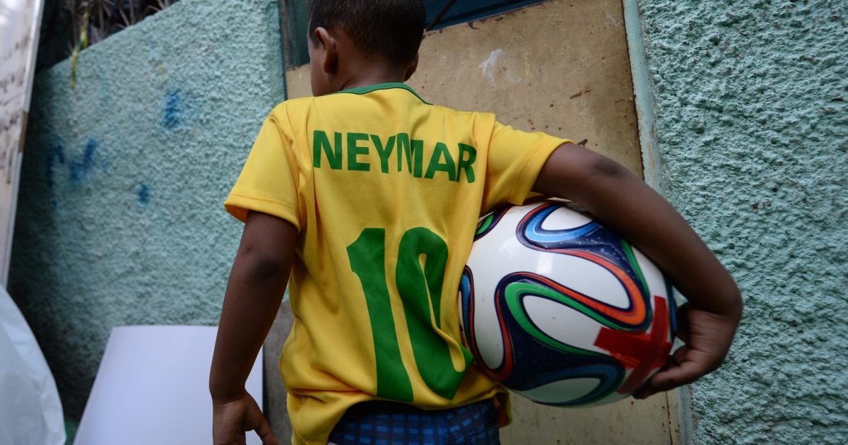 A boy of the Jacarezinho shantytown walks with a football after decorating the streets and houses of the neighborhood for the upcoming FIFA World Cup, in Rio de Janeiro.</p>