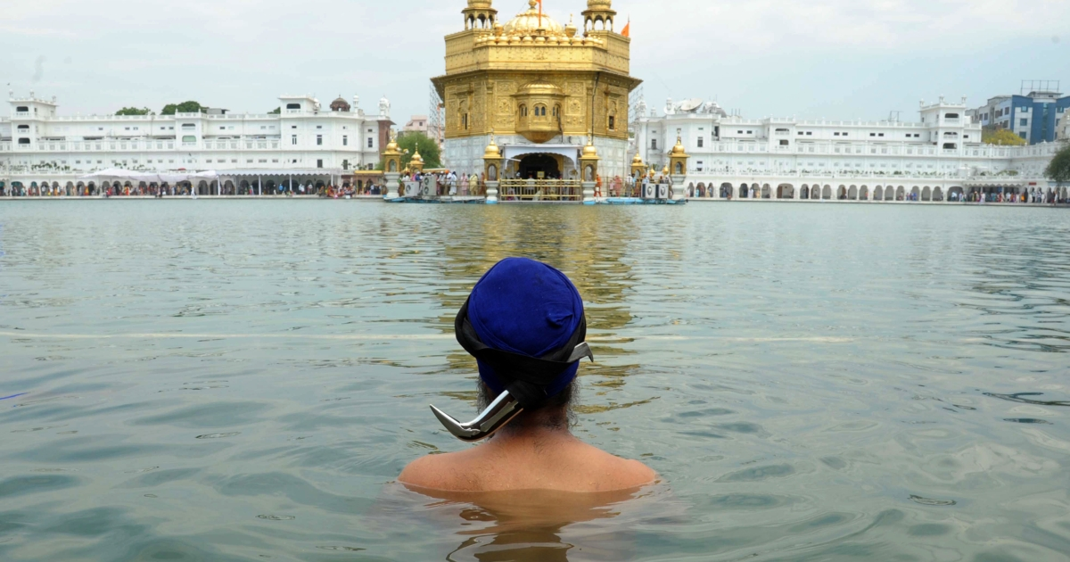 An Indian Sikh devotee takes a dip at the Golden Temple in Amritsar on May 23, 2014, on the occasion of the 535th birth anniversary of Guru Amardas, the third master of the Sikhs. It's the same temple that was attacked by Indian troops in 1984.</p>