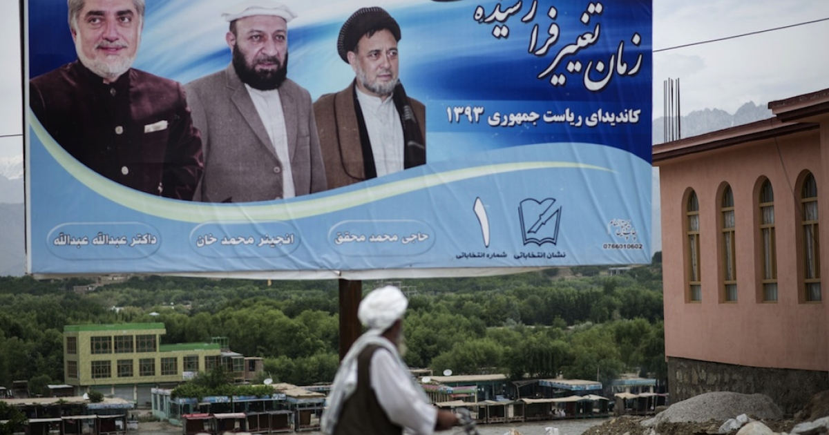 An Afghan man looks at an election billboard along a street near Bagram Airfield in Parwan on May 29, 2014.  Two candidates, Ashraf Ghani and Abdullah Abdullah will compete in the run-off on June 14 to determine who leads Afghanistan into a new era without the assistance of NATO combat troops to help fight the Taliban insurgency.</p>