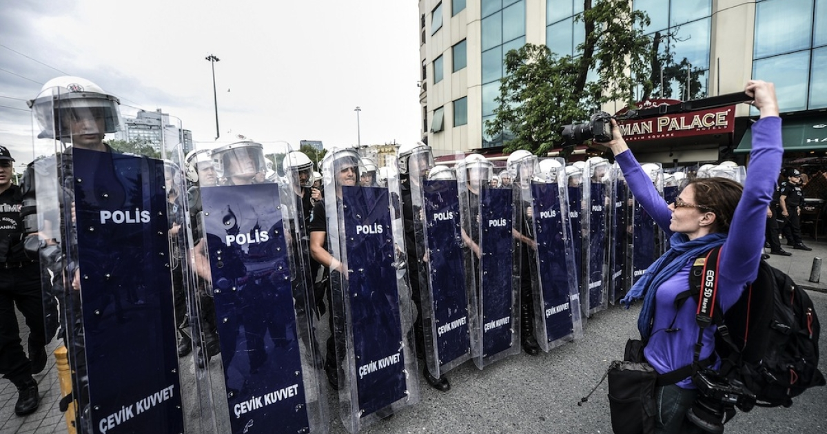 A photographer takes a photo of Turkish riot police officers standing in line as they block access to Taksim square on May 31, 2014, during the one year anniversary of the Gezi park and Taksim square demonstrations.</p>