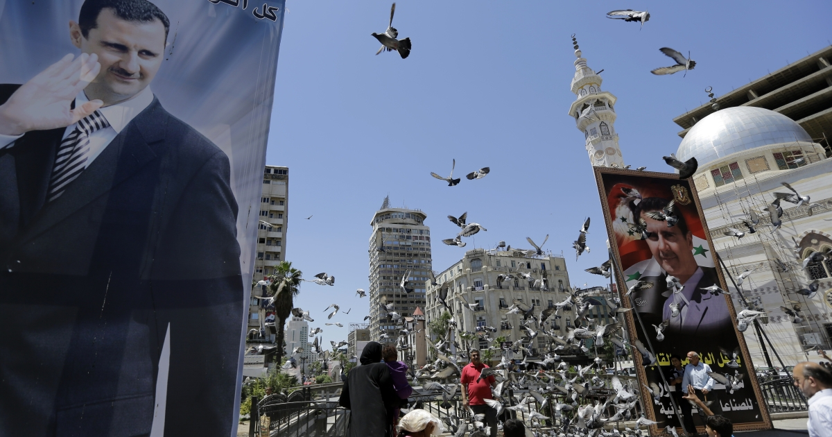 Syrians feed pigeons on a square where are displayed giant campaign billboards bearing portraits of Syrian President Bashar al-Assad on June 1, 2014 in the capital Damascus.</p>