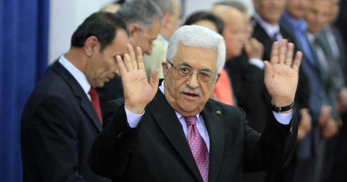 Palestinian president Mahmoud Abbas waves during the swearing-in ceremony of the new Palestinian unity government. The caption AFP filed with this photo says that he is