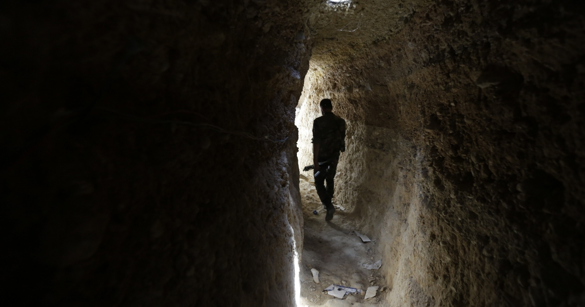 A Syrian army soldier makes his way in a tunnel reportedly previously used by rebel fighters in Jobar.</p>